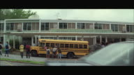 WS ZI School bus and group of teenagers in front of high school / Mechanicsville, Atlanta, Georgia, USA