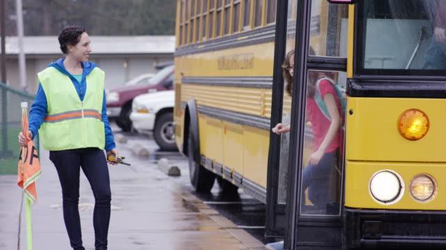 School bus attendant ushering elementary students off of bus