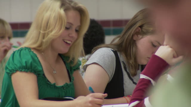 CU School children (14-16) at study hall table, girls writing in notebooks, Cazenovia, New York, USA
