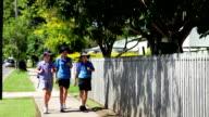 School children girls in uniform walking on footpath towards camera