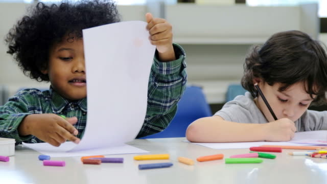 School children, happy little boys drawing with colors and crayons