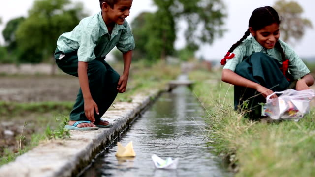 School children playing with paper boat near water canal