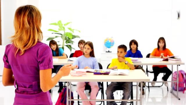 School children raising hands in classroom.