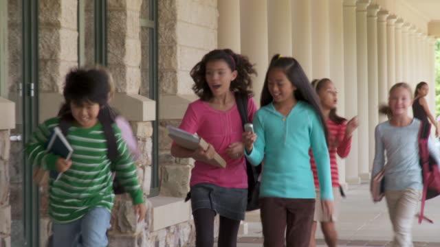 MS, School children text messaging, walking outside classrooms , Richmond, Virginia, USA