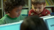 CU, SELECTIVE FOCUS, PAN, School children (6-9) using laptops with teacher in classroom, Richmond, Virginia, USA,