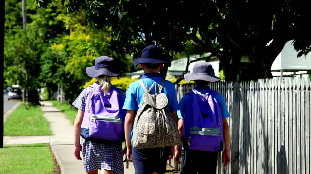 School Children Walking to school rear view unrecognizable