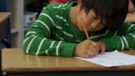 CU, PAN, TU, TD, School girl (10-11) thinking sitting over test in classroom, Richmond, Virginia, USA