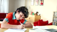 School kid does his homework looks up and smiles