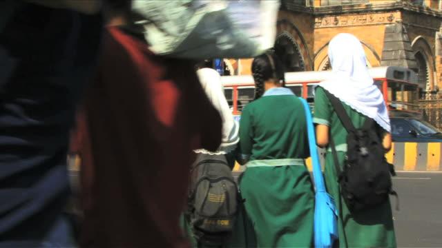 School kids in formal dress crossing road Mumbai, India
