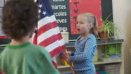 CU, SHAKY, School pupils (6-9)reciting pledge holding American flag in classroom, Richmond, Virginia, USA