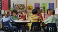 MS, School pupils (6-9) sitting at desk with teacher in classroom, Richmond, Virginia, USA
