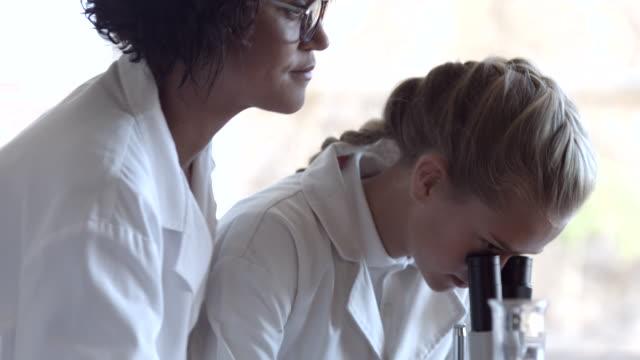 CU School teacher assisting children in science lab