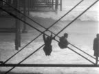Schoolboys stand on the support structure of Brighton's Palace Pier as waves roll onto the shore