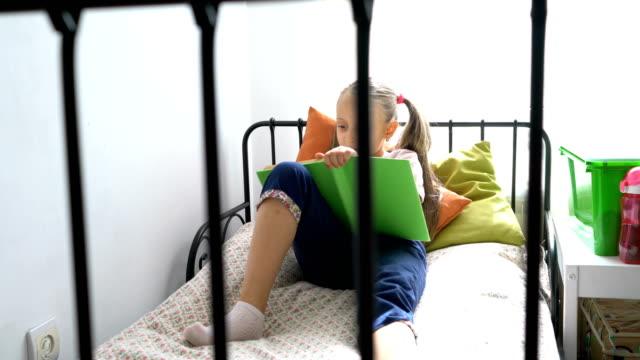 Schoolgirl reading book in her room