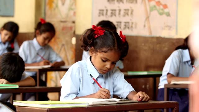 Schoolgirl studying in classroom, Haryana, India
