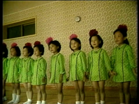 Schoolgirls in colourful uniform stand in line singing North Korea Feb 88