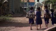 MS Schoolgirls in uniforms with backpacks walking away down dirt road in poor village, Pune, Maharashtra, India