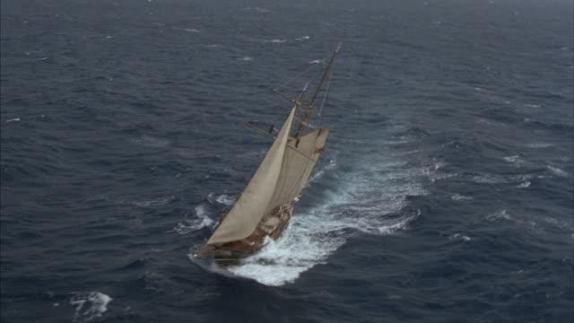 A schooner makes a turn under full sails at sea.