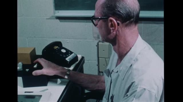Scientist astronomer in laboratory examining printed black amp white images of eclipse solar corona Astronomy solar physics science