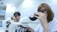 HD : Scientist Couple using microscope