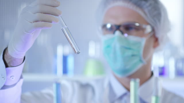 Wetenschapper, arts, student, in schone pak onderzoeken monster in een reageerbuis