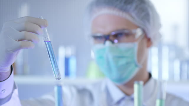 Forskare, läkare, student, i ren kostym att undersöka urval i provrör