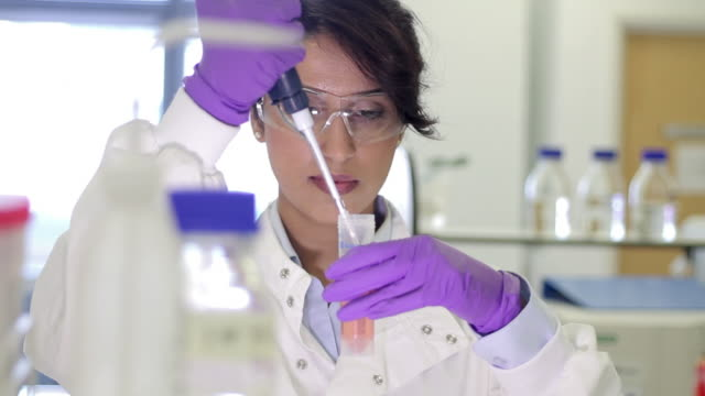 Scientist dropping liquid into vial in genetic laboratory