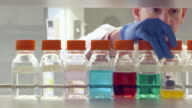 MS Scientist examining bottles of solution on shelf in research laboratory