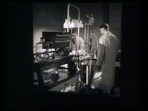 Scientist in animal lab male scientist injecting dog w/ needle CU of readout another doctor checking scans Animal testing science biology