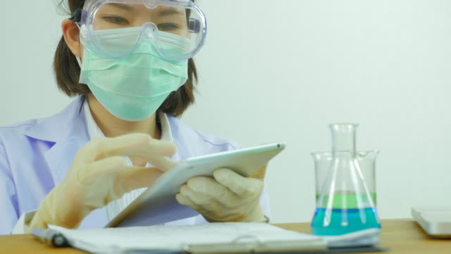 Scientist is using tablet . Front view. From right to left.