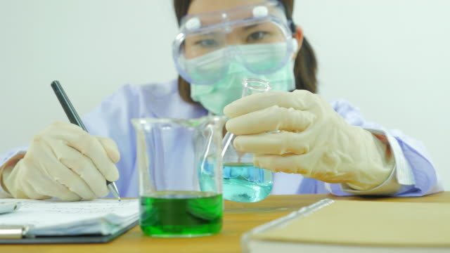 Scientist is writing note on paper.Front view. From right to left.