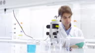 MS Scientist looking through microscope in research laboratory and taking notes on notepad