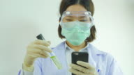 Scientist notice the substance and searching some information on mobile. Front view. From right to left.