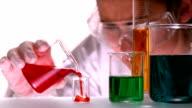 Scientist pouring red liquid into beaker