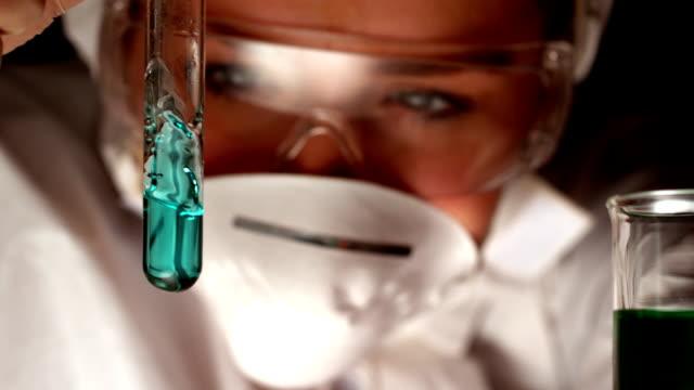 Scientist swirling blue liquid in test tube