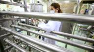 Scientist using digital tablet in pharmaceutical factory.