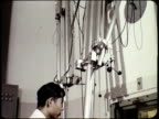 1963 MONTAGE Scientist using remote handling equipment in laboratory; Man being treated for cancer with radiation machine / Japan