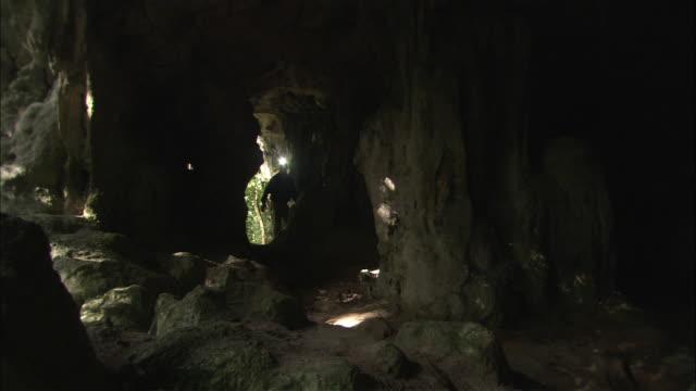 A scientist with a headlamp walks inside a dark cave.