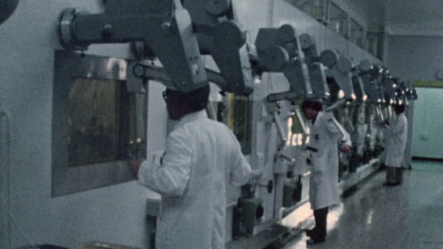 1983 WS Scientists working in laboratory, using mechanical arms to manipulate experiments behind protective glass / United Kingdom