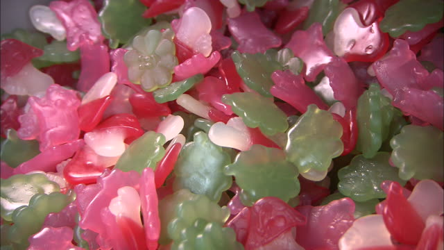 A scoop removes green and pink gummie candies from a bin.