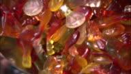 A scoop scoops gummie candies from a bin.