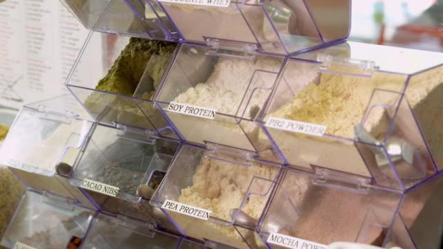 CU scooper spoon retrieves a scoop of hemp protein powder booster and PEA protein powder booster at juice bar as smoothie ingredients