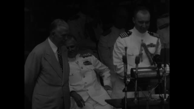 Scores of midshipmen with one row standing as man walks to stage / US Defense Secretary George Marshall shakes cadet's hand and gives him bundle as...