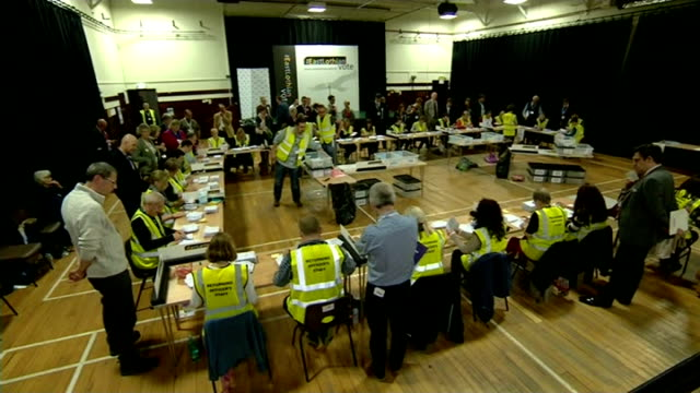 ITV News Special Clean Feed 0100 0200 People in counting hall East Renfrewshire 'East Renfrewshire Referendum Count' sign TILT DOWN people counting...