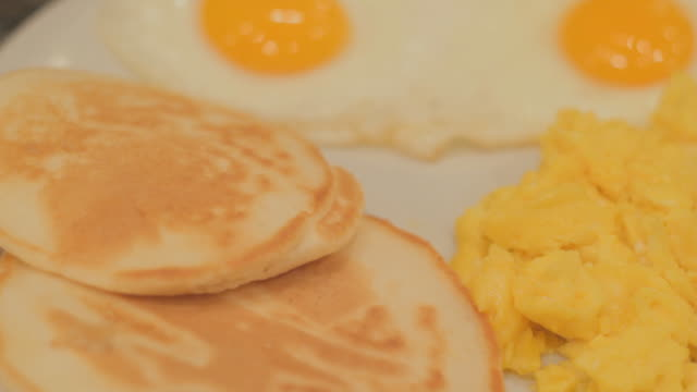 Scrambled eggs, two combined fried eggs and two biscuits on a white plate 2