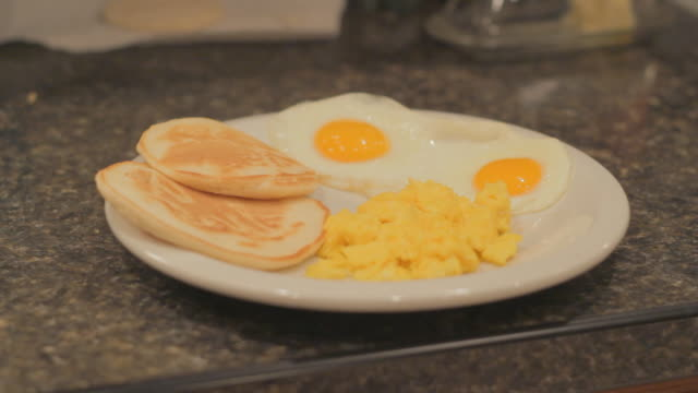 Scrambled eggs, two combined fried eggs and two biscuits on a white plate 5