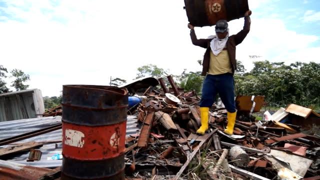 Scrap dealer carries old Texaco barrel inside Amazonian dumpster