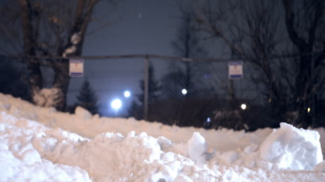 A scraper pushes the snow