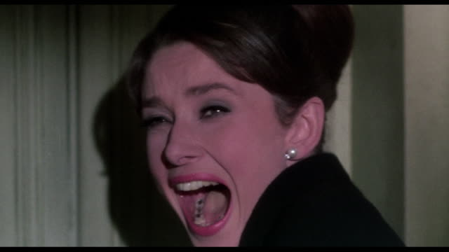 Screaming woman (Audrey Hepburn) discovers threatening man (George Kennedy) with metal hand ransacking her room