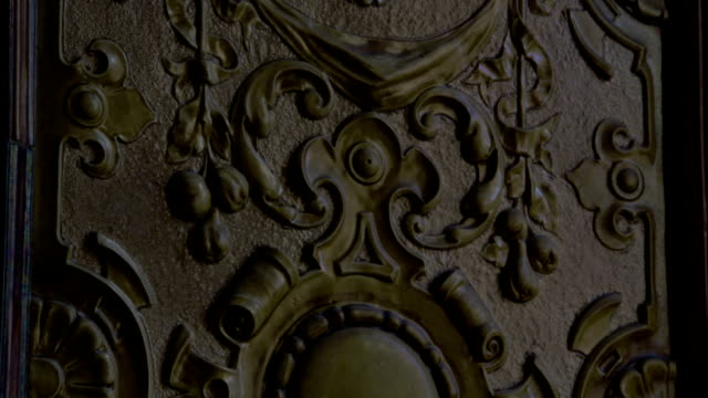 Scrollwork covers a metal plaque. Available in HD.
